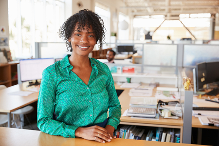 Black female architect in open plan office smiling to camera Banco de Imagens