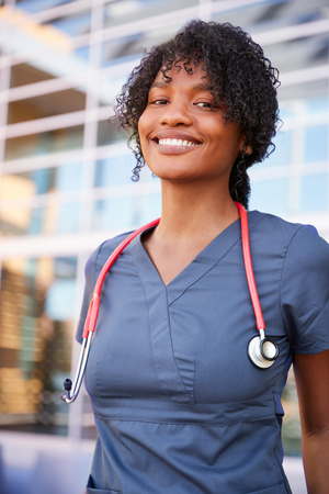 Smiling black female healthcare worker outdoors, vertical Stock Photo