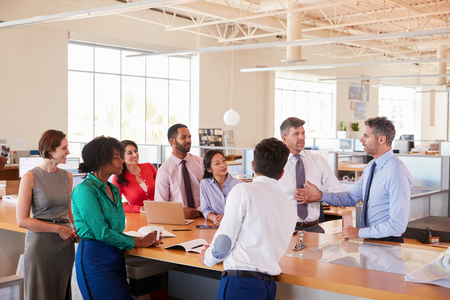 Businessman addressing team at a meeting in open plan office