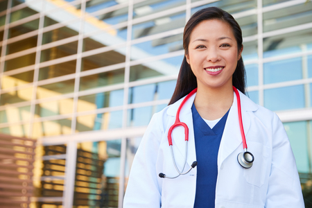 Smiling Asian female healthcare worker outdoors in lab coat