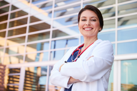 Smiling Hispanic female healthcare worker with arms crossed
