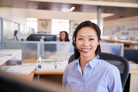 Mujer asiática joven que trabaja en un centro de llamadas sonriendo a la cámara Foto de archivo