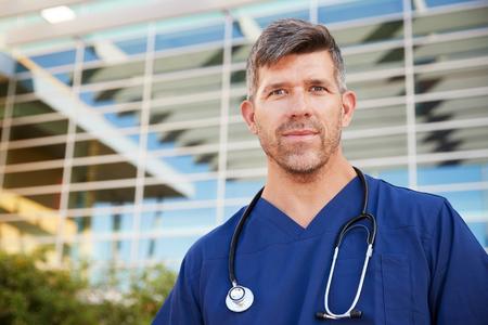 White male healthcare worker outside modern hospital