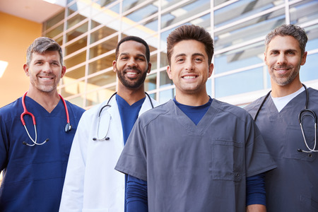 Four male healthcare colleagues standing outdoors, portrait