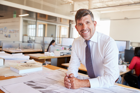 Middle aged male architect smiling to camera in his office Фото со стока