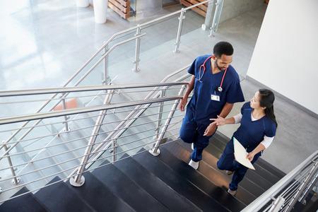 Dos colegas de la salud hablando en las escaleras del hospital Foto de archivo