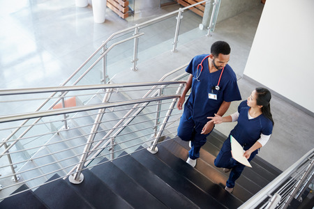 Two healthcare colleagues talking on the stairs at hospital Banco de Imagens