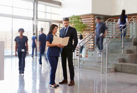 Zwei Angestellte des Gesundheitswesens unterhalten sich in der Lobby eines geschäftigen Krankenhauses