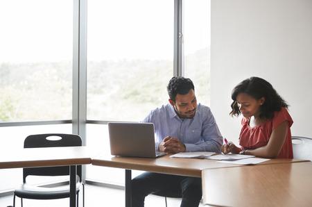 Tuteur de lycée donnant une étudiante avec un ordinateur portable un à un des frais de scolarité au bureau