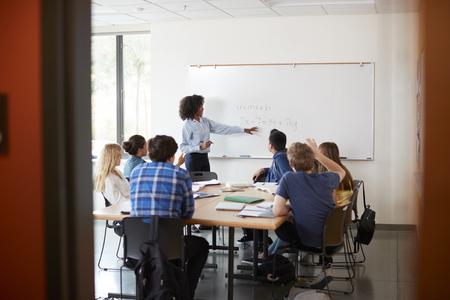 Vista attraverso la porta del tutor di scuola superiore alla lezione di matematica di insegnamento della lavagna