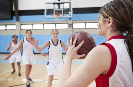 Female High School Basketball Team Passing Ball On Court