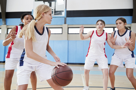 Female High School Basketball Team Dribbling Ball On Court