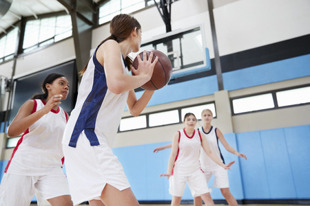 Female High School Basketball Team Passing Ball On Court