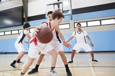 Male High School Basketball Team Dribbling Ball On Court Stock Photo