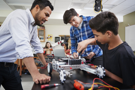 Teacher With Male Pupils Building Robotic Vehicle In Science Lesson