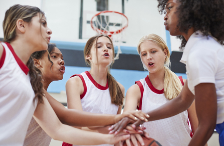 Female High School Basketball Players Joining Hands During Team Talk With Coach