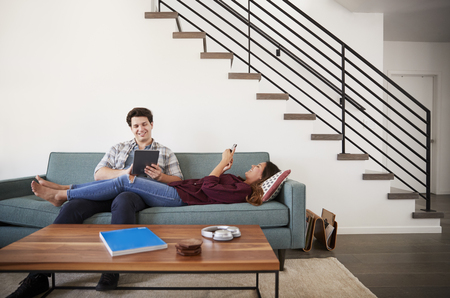 Couple Relaxing On Sofa At Home Using Mobile Phone And Digital Tablet