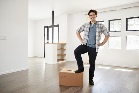 Portrait Of Proud Man Standing On Box In New Home On Moving Day