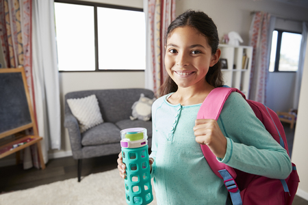 Portrait Of Girl With Backpack In Bedroom Ready To Go To School Standard-Bild
