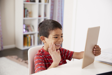 Young Boy Sitting At Desk In Bedroom Using Digital Tablet To Make Video Call