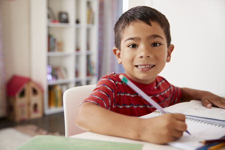 Portrait Of Young Boy Sitting At Desk In Bedroom Doing Homework 免版税图像