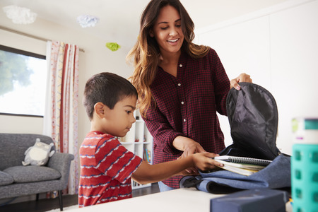 Mother In Bedroom Helping Son To Pack Bag Ready For School