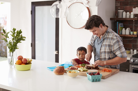 Father And Son Making School Lunch In Kitchen At Home Stock Photo