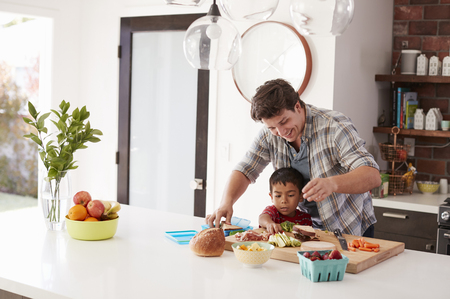 Father And Son Making School Lunch In Kitchen At Home 版權商用圖片