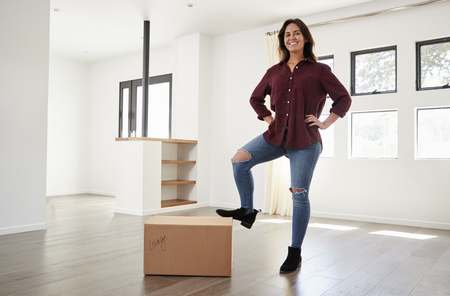 Portrait Of Proud Woman Standing On Box In New Home On Moving Day