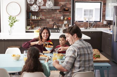 Familia disfrutando de la comida alrededor de la mesa en casa juntos