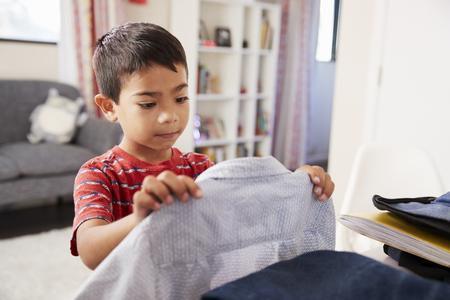 Boy In Bedroom Choosing Shirt Ready For School