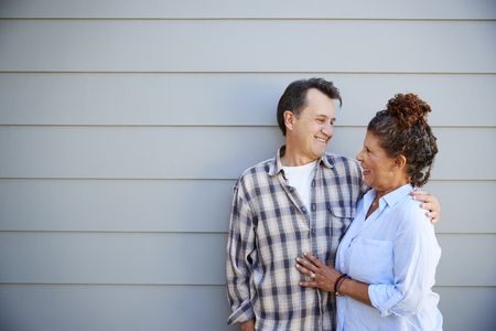 Senior Couple Standing Outside Grey Clapboard House