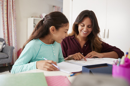 Mother Helping Daughter With Homework Sitting At Desk In Bedroom Stock Photo