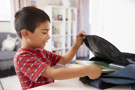 Boy In Bedroom Packing Bag Ready For School