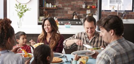 Famille multi-génération appréciant les repas autour de la table à la maison ensemble