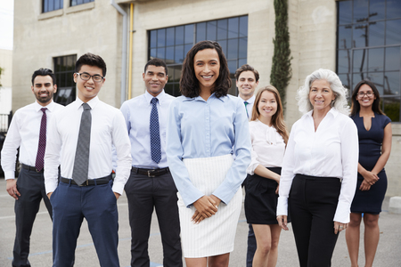 Young businesswoman and colleagues outdoors, portrait