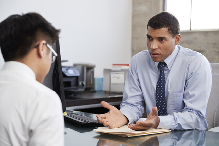 Concerned mixed race male therapist counselling male patient