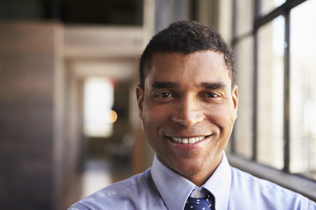 Close up portrait of smiling mixed race businessman Stock Photo