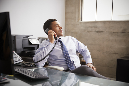 Mixed race businessman at an office desk using the phone