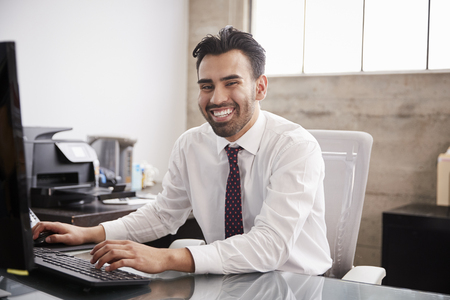 Young Hispanic businessman using computer smiling to camera