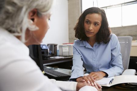 Betroffene weibliche Analytikerin berät ältere Patientin Standard-Bild