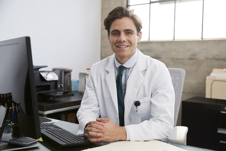 Young white male doctor at desk, portrait Stock Photo