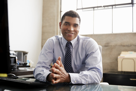 Mixed race businessman at an office desk smiling to camera Stock Photo