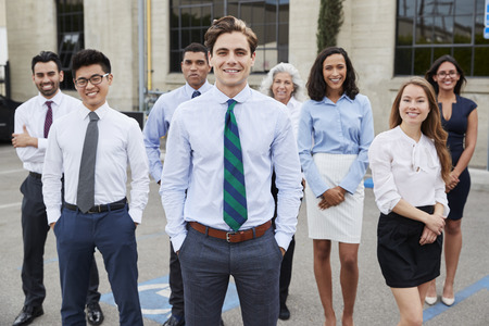 Young white businessman and colleagues outdoors, portrait Stock Photo