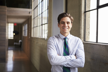 Young white businessman stands smiling with arms crossed