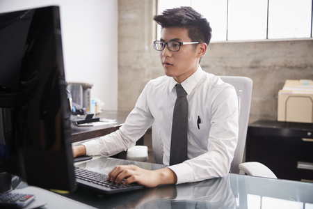 Young Asian businessman using a computer at an office desk Stock Photo