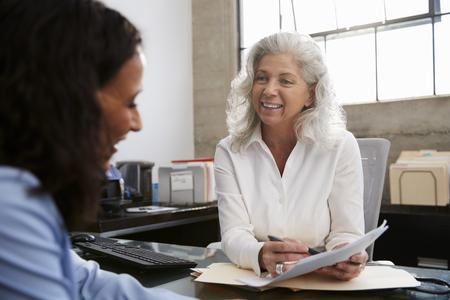 Senior professionele vrouw vergadering in kantoor met jonge vrouw