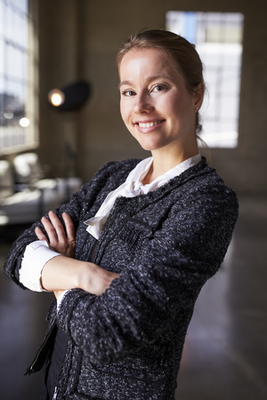 Young white businesswoman with arms crossed smiles to camera