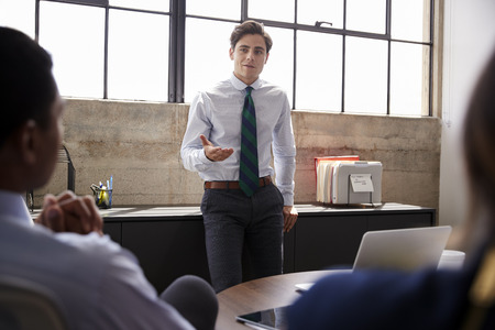 Young male manager addressing team at a meeting, close up Stock Photo