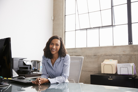 Young mixed race woman at office desk smiling to camera